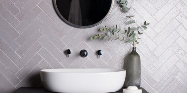 vanity with white sink, small plant and grey wall tile