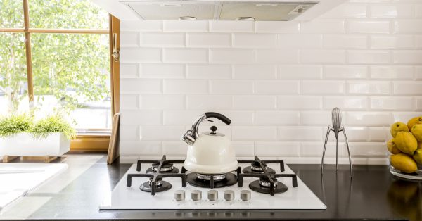 white kitchen backsplash with white stove and black burners and countertops