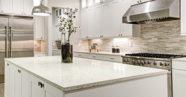 white marble countertops with white cabinets and grey backsplash