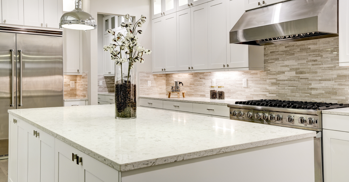 well lit kitchen with white island and white countertops and grey patterned backsplash